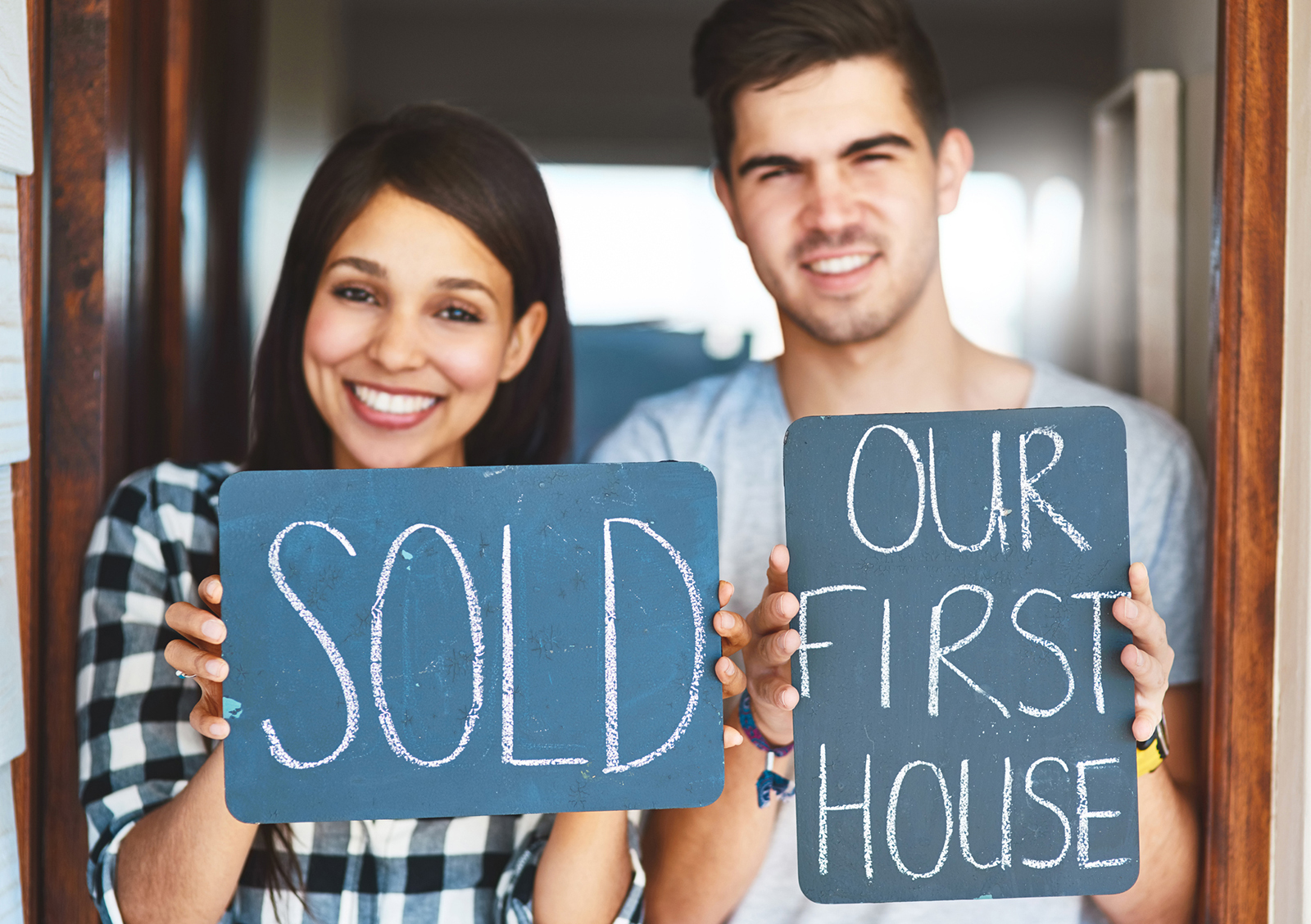 Portrait of a happy couple holding signs as they move into their new house